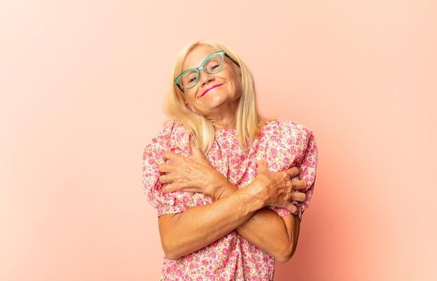 Frau mittleren alters, die fröhlich und selbstbewusst mit einem lässigen, glücklichen, freundlichen lächeln lacht