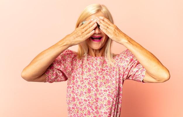 Frau mittleren alters, die gesicht mit händen bedeckt, mit überraschtem ausdruck zwischen den fingern späht und zur seite schaut