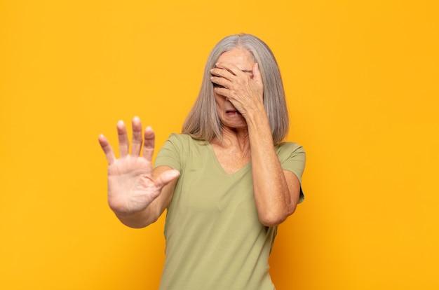 Frau mittleren alters, die gesicht mit hand bedeckt und andere hand nach vorne legt, um kamera zu stoppen, fotos oder bilder ablehnend