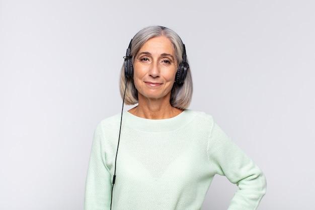 Frau mittleren alters, die glücklich mit einer hand auf der hüfte und selbstbewusster, positiver, stolzer und freundlicher haltung lächelt. musikkonzept