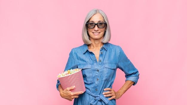 Frau mittleren alters, die glücklich mit einer hand auf hüfte lächelt und zuversichtlich isoliert