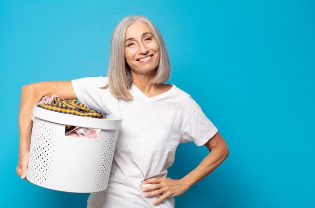 Frau mittleren alters, die glücklich mit einer hand auf hüfte und selbstbewusster, positiver, stolzer und freundlicher haltung lächelt