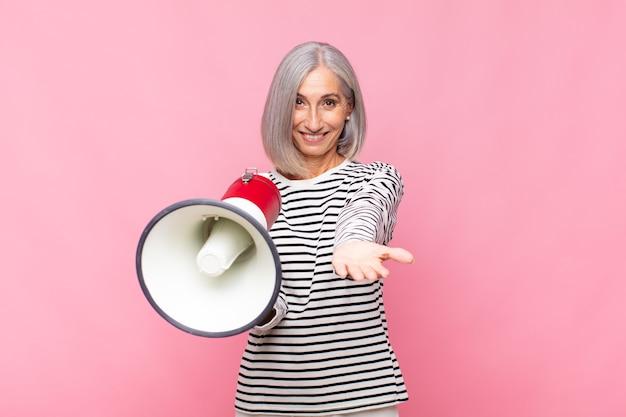 Frau mittleren alters, die glücklich mit freundlichem, selbstbewusstem, positivem blick lächelt und ein objekt oder konzept mit einem megaphon anbietet und zeigt
