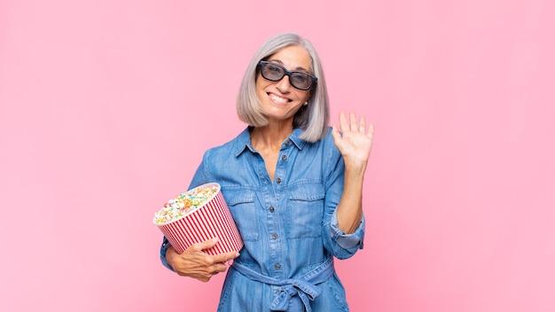 Frau mittleren alters, die glücklich und fröhlich lächelt, hand winkt, sie begrüßt und begrüßt oder abschiedsfilmkonzept sagt
