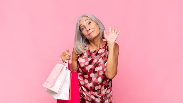 Frau mittleren alters, die glücklich und fröhlich lächelt, hand winkt, sie begrüßt und begrüßt oder sich mit einkaufstüten verabschiedet
