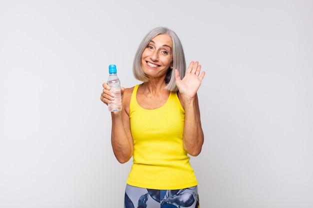 Frau mittleren alters, die glücklich und fröhlich lächelt, hand winkt, sie begrüßt und begrüßt oder sich verabschiedet. fitness-konzept