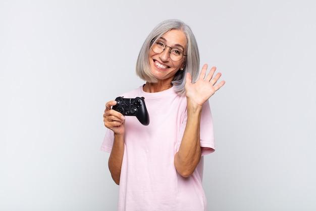 Frau mittleren alters, die glücklich und fröhlich lächelt, hand winkt, sie begrüßt und begrüßt oder sich verabschiedet. spielkonsolenkonzept