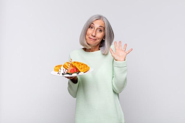 Frau mittleren alters, die glücklich und fröhlich lächelt, hand winkt, sie begrüßt und begrüßt oder sich verabschiedet