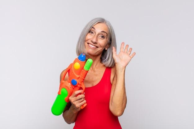 Frau mittleren alters, die glücklich und fröhlich lächelt und hand winkt