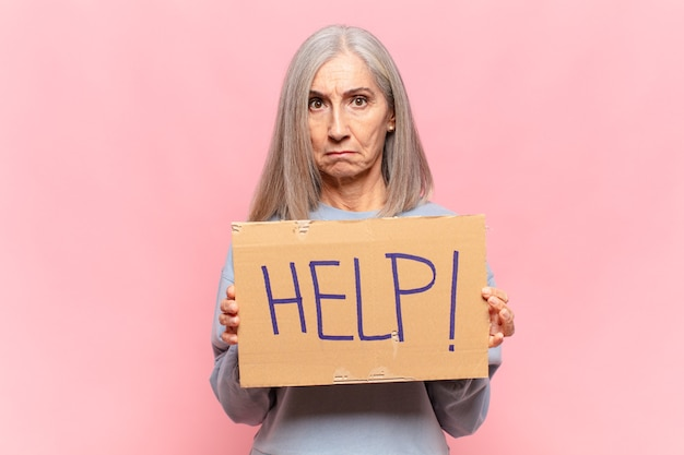 Frau mittleren alters, die hilfebrett hält