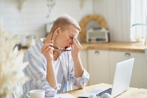 Frau mittleren alters, die ihre nase massiert und sich schläfrig fühlt, während sie online von zu hause aus am laptop arbeitet