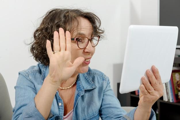Frau mittleren alters, die im internet einen entfernten anruf tätigt