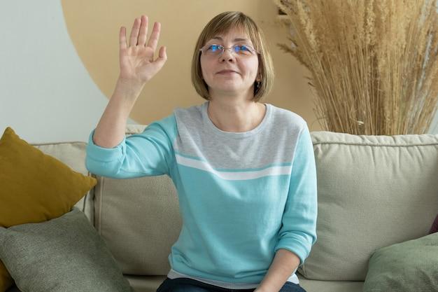 Frau mittleren alters, die kamera ältere frau in brille betrachtet, ruft zu hause an