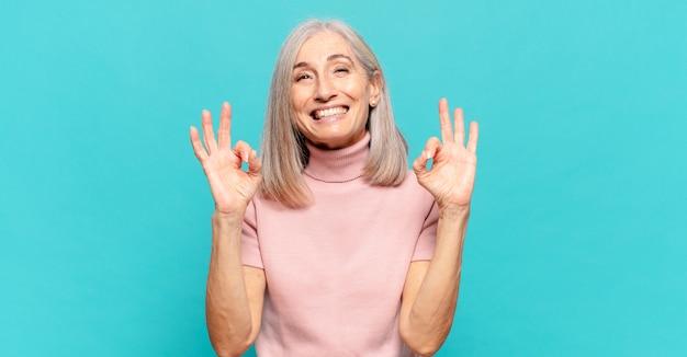 Frau mittleren alters, die konzentriert und meditierend aussieht, sich zufrieden und entspannt fühlt, denkt oder eine wahl trifft