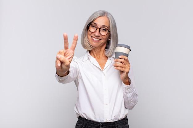 Frau mittleren alters, die lächelt und freundlich schaut, nummer zwei oder sekunde mit der hand vorwärts zeigend, kaffeekonzept herunterzählend