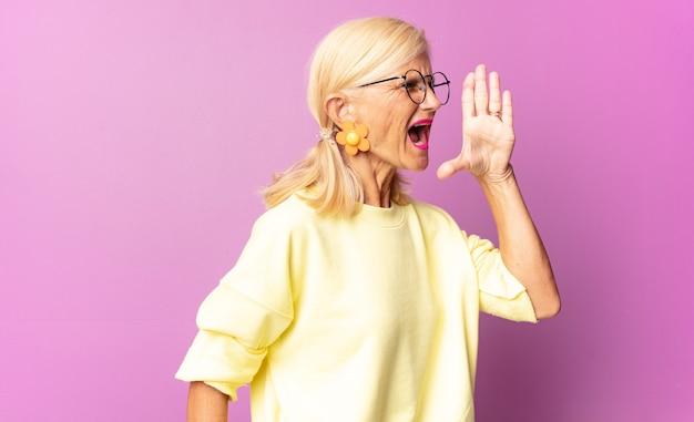 Frau mittleren alters, die laut und wütend schreit, um platz auf der seite zu kopieren, mit der hand neben dem mund