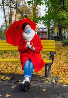 Frau mittleren alters, die medizinische schutzmaske trägt, die mit rotem regenschirm auf gelber bank im herbstpark sitzt