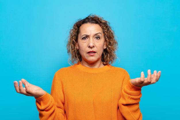 Frau mittleren alters, die mit einem dummen, verrückten, verwirrten, verwirrten ausdruck die achseln zuckt, sich genervt und ahnungslos fühlt