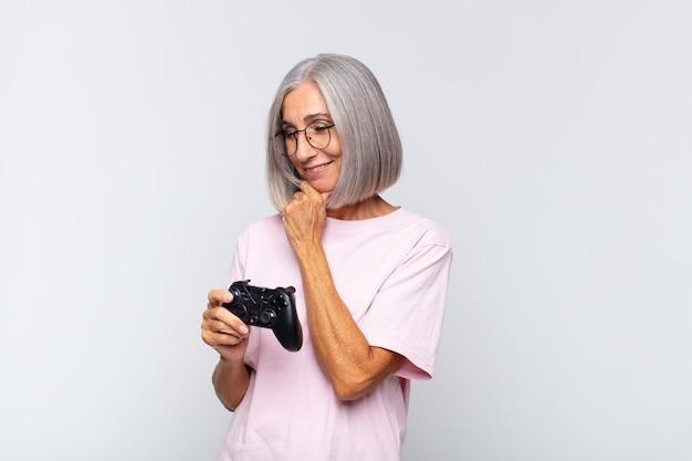 Frau mittleren alters, die mit einem glücklichen, selbstbewussten ausdruck mit der hand am kinn lächelt, sich wundert und zur seite schaut. spielkonsolenkonzept