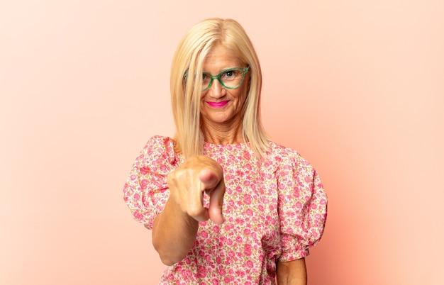 Frau mittleren alters, die mit einem zufriedenen, selbstbewussten, freundlichen lächeln auf die kamera zeigt und sie wählt