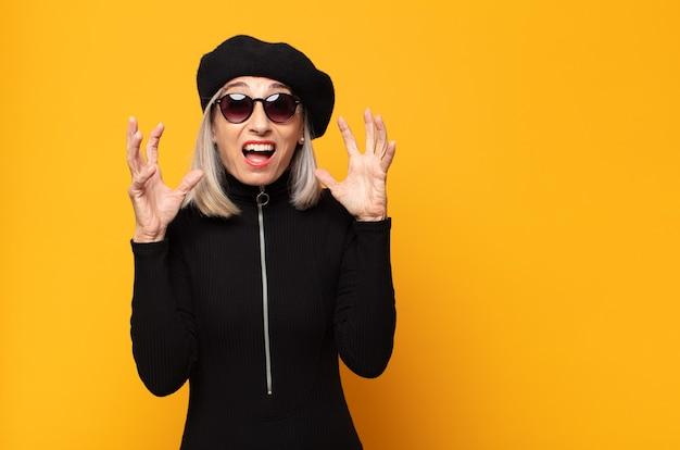 Frau mittleren alters, die mit erhobenen händen schreit und sich wütend, frustriert, gestresst und verärgert fühlt Premium Fotos