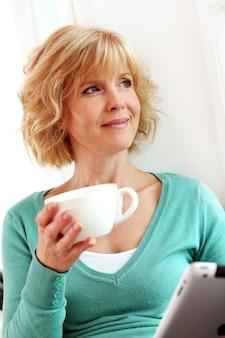 Frau mittleren alters, die mit tablette comper entspannt