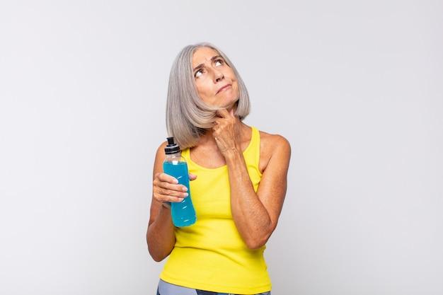 Frau mittleren alters, die nachdenkt, sich zweifelnd und verwirrt fühlt, mit verschiedenen optionen und sich fragt, welche entscheidung sie treffen soll. fitnesskonzept