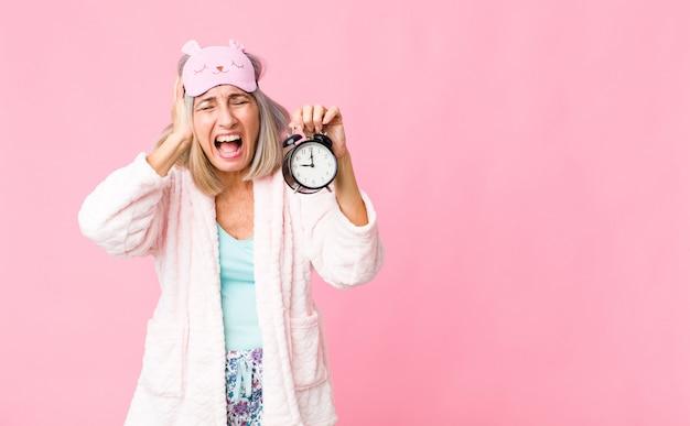 Frau mittleren alters, die nachtanzug mit einem wecker trägt