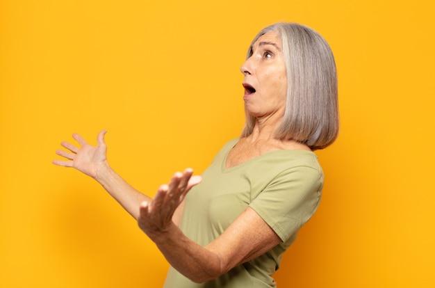 Frau mittleren alters, die oper aufführt oder bei einem konzert oder einer show singt und sich romantisch, künstlerisch und leidenschaftlich fühlt