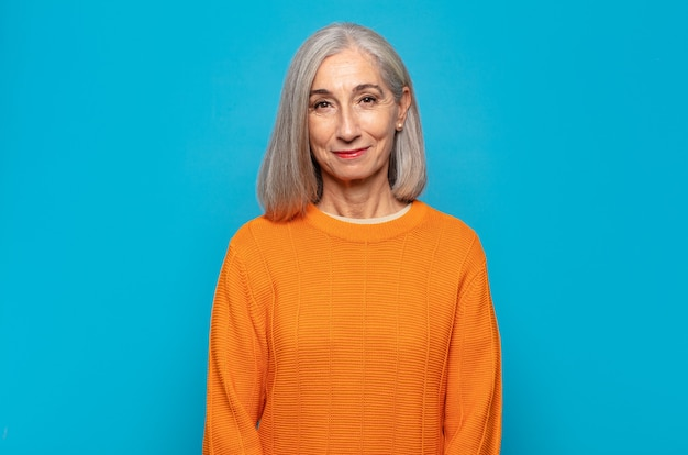 Frau mittleren alters, die positiv und selbstbewusst lächelt und zufrieden, freundlich und glücklich aussieht