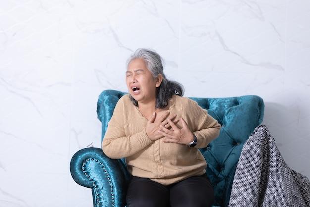 Frau mittleren alters, die schmerzen empfindet, die die brust berühren und zwischen den reisen einen herzinfarkt haben.