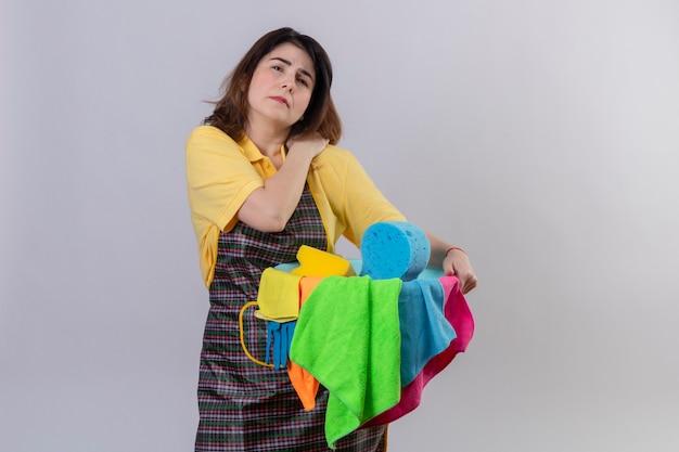 Frau mittleren alters, die schürze hält, die eimer mit reinigungswerkzeugen hält, die unwohl schauen, ihre schulter berührend, die schmerzen haben, die über weißer wand stehen