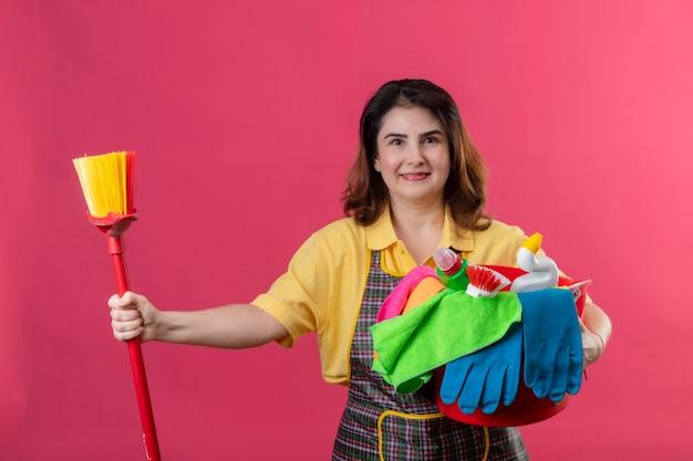 Frau mittleren alters, die schürze hält eimer mit reinigungswerkzeugen und mopp lächelnd fröhlich positiv und glücklich zeigt daumen hoch stehend über rosa wand