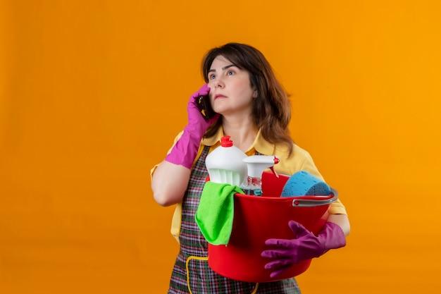 Frau mittleren alters, die schürze und gummihandschuhe trägt, die eimer mit reinigungswerkzeugen halten, die auf handy mit ernstem ausdruck auf gesicht stehen, das über orange wand steht
