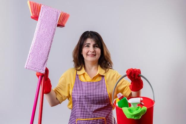 Frau mittleren alters, die schürze und gummihandschuhe trägt, die eimer mit reinigungswerkzeugen halten