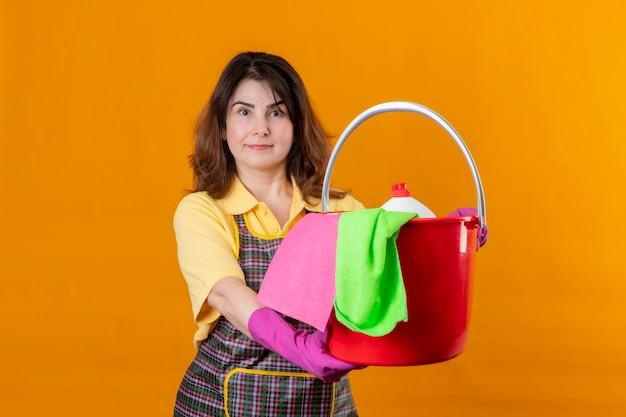Frau mittleren alters, die schürze und gummihandschuhe trägt, die eimer mit reinigungswerkzeugen mit ernstem selbstbewusstem ausdruck auf lächelndem freundlichem stehen über orange wand halten