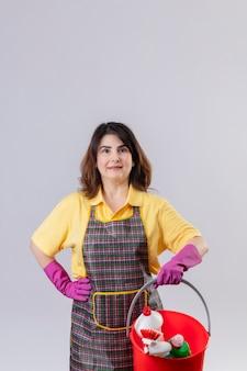 Frau mittleren alters, die schürze und gummihandschuhe trägt, hält eimer mit reinigungswerkzeugen, die kamera mit ernstem sicherem ausdruck auf gesicht lächeln, das freundlich bereit ist, über weißem hintergrund zu reinigen