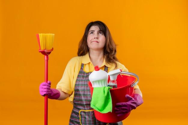 Frau mittleren alters, die schürze und gummihandschuhe trägt, hält eimer mit reinigungswerkzeugen und mopp, der mit nachdenklichem ausdruck auf gesicht denkend betrachtet und zweifel hat, die über orange wand stehen