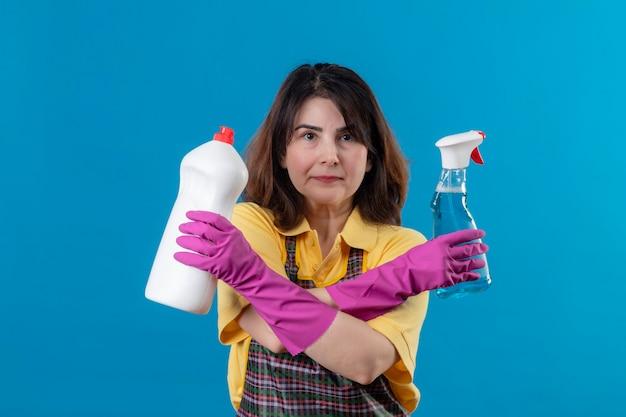 Frau mittleren alters, die schürze und gummihandschuhe trägt und reinigungsmittel hält, die mit verschränkten armen stehen