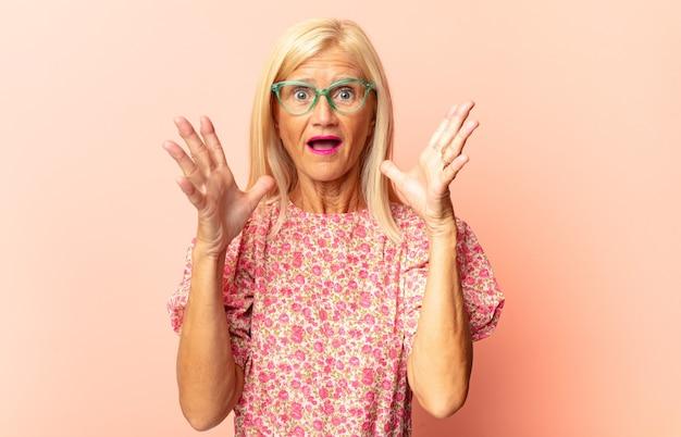 Frau mittleren alters, die sehr schockiert oder überrascht aussieht und mit offenem mund starrt und wow sagt