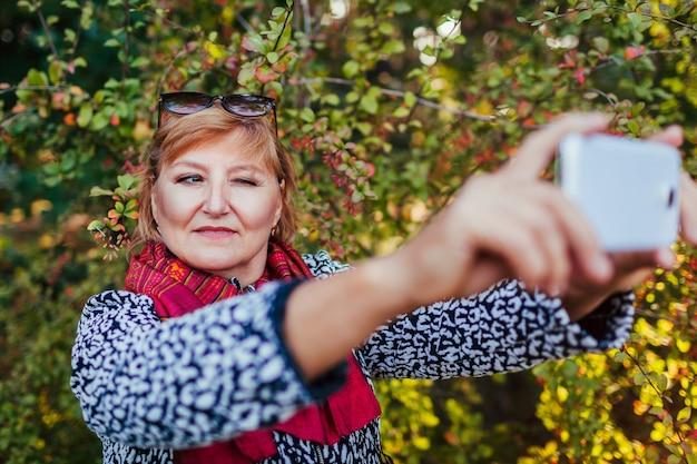Frau mittleren alters, die selfie am telefon macht und im park spazieren geht. ältere dame, die spaß im herbstwald hat