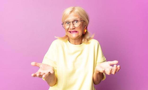 Frau mittleren alters, die sich ahnungslos und verwirrt fühlt, sich nicht sicher ist, welche wahl oder option sie wählen soll, und sich wundert