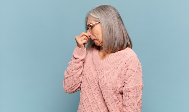 Frau mittleren alters, die sich angewidert fühlt und die nase hält, um einen üblen und unangenehmen gestank zu vermeiden