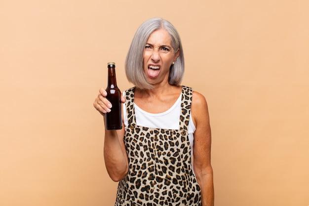 Frau mittleren alters, die sich angewidert und gereizt fühlt, die zunge herausstreckt und etwas böses und glückliches mit einem bier nicht mag
