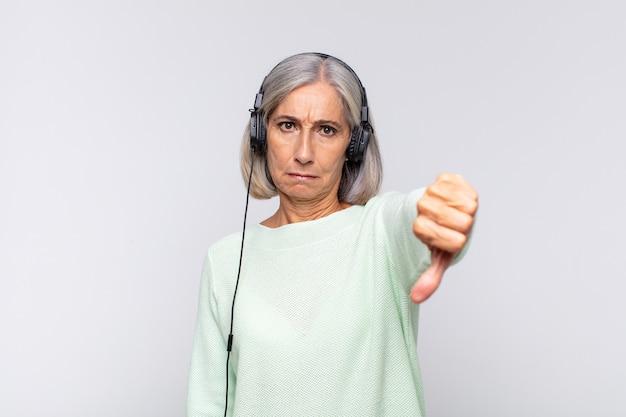 Frau mittleren alters, die sich böse, wütend, verärgert, enttäuscht oder unzufrieden fühlt und mit ernstem blick die daumen nach unten zeigt