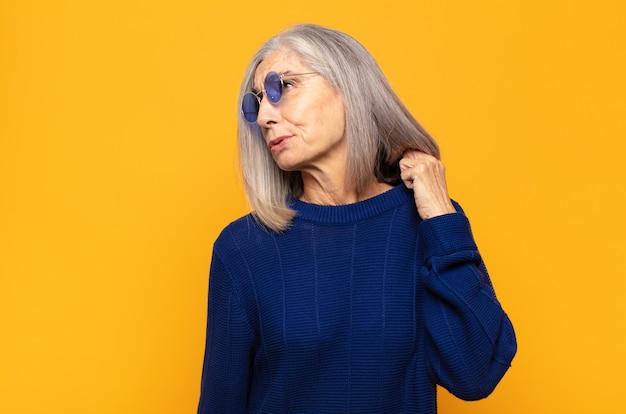 Frau mittleren alters, die sich gestresst, ängstlich, müde und frustriert fühlt, den hemdhals zieht und mit dem problem frustriert aussieht