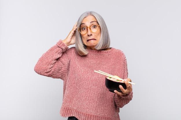 Frau mittleren alters, die sich gestresst, besorgt, ängstlich oder verängstigt fühlt, mit den händen auf dem kopf, die über das fehlerhafte asiatische nahrungsmittelkonzept in panik geraten