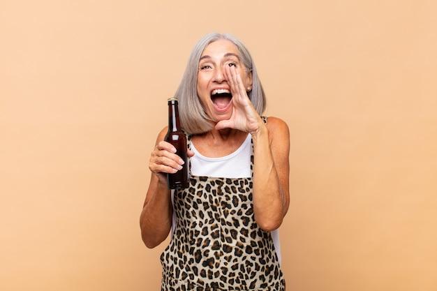 Frau mittleren alters, die sich glücklich, aufgeregt und positiv fühlt, mit den händen neben dem mund einen großen schrei ausstößt und mit einem bier ruft