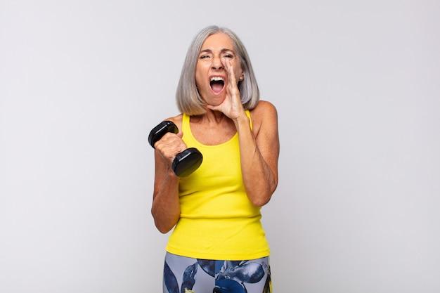 Frau mittleren alters, die sich glücklich, aufgeregt und positiv fühlt, mit den händen neben dem mund einen großen schrei ausstößt und ruft. fitness-konzept