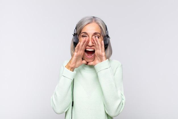 Frau mittleren alters, die sich glücklich, aufgeregt und positiv fühlt, mit den händen neben dem mund einen großen schrei ausstößt und ruft. musikkonzept